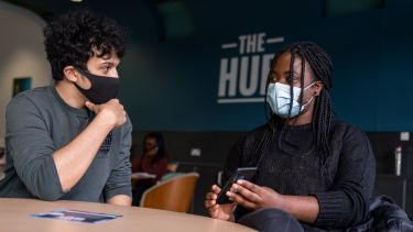 2 students socialising in edge hub on phones with face coverings