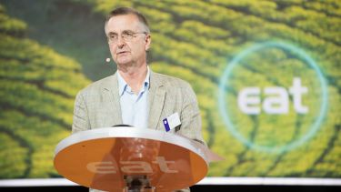 Professor Tim Lang from City University of London speaking at a lectern with a green background