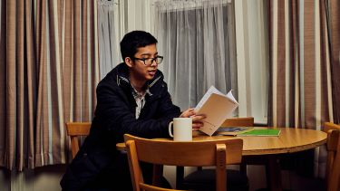 Photo of student sat at dining table reading a book