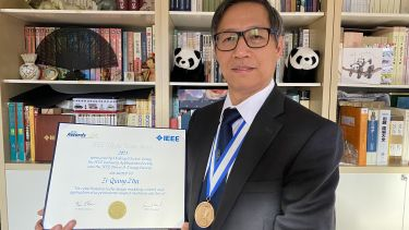 Prof Zhu wearing his IEEE Tesla medal and holding his certificate