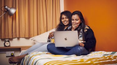 Photo of two students sat on a bed laughing at a laptop screen