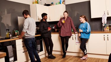 Four students stood in a kitchen laughing and drinking tea