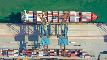 An overhead view of cargo containers being loaded onto a cargo ship