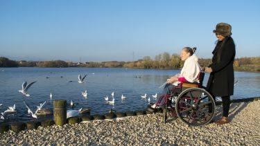 A wheelchair user and her carer visit a park, they are next to a pond with birds.