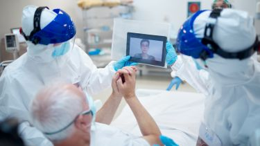 A patient in a hospital bed being assisted by staff to make a video call.