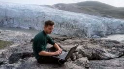 Alumnus Olly Bartlett sitting with a laptop in front of an ice sheet