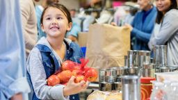 Picture of a girl holding a bag of apples in a food bank