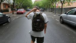 A shot of a male student from behind walking alone down a road.