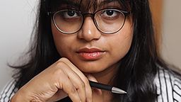 A profile photograph of masters student Umanga Perera. She is holding a pen.
