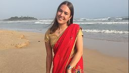 Charlotte Pritchard stood on the beach in a sari whilst on her placement abroad