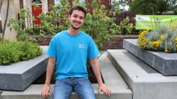 Dario Trimarchi in blue University of Sheffield student ambassador t shirt, sitting outside HRI building and smiling at camera