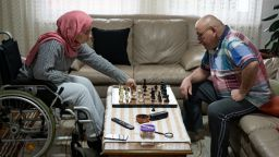 A woman and her grandfather playing chess in a living room