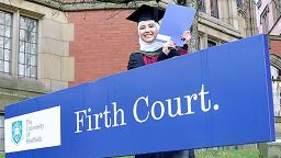 Nora stood in front of the Firth Court sign at her graduation