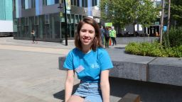 Student ambassador Sophie sitting in the sun and smiling outside Jessop West Building