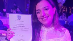 Andra-Maria smiling, at her graduation after-party, holding her certificate