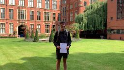 Chris standing in the courtyard at Firth Court, smiling and holding a certificate