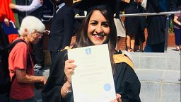 Sonia Nayyar in her graduation gown holding her degree certificate