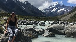 Laura Tracey sat on a rock in front of some mountains and a river