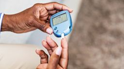 Photograph of elderly person testing their blood sugar level.