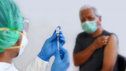 Close-Up Of Doctor Preparing Syringe For Patient - stock photo